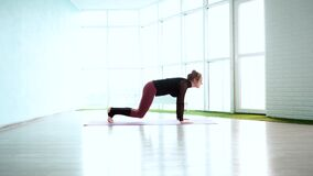 Flexible young woman practicing in Downward Facing Dog pose in light yoga studio