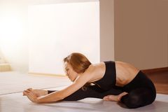 Flexible young woman stretching her right leg in gym. Young beautiful woman in sportswear doing stretching while sitting on the floor Stock Images