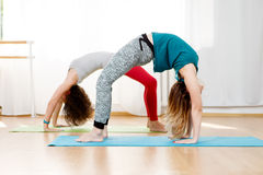 Flexible young women practice chakrasana asana in yoga studio Stock Photos