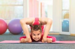 Flexibler Turner des kleinen Mädchens, der akrobatische Übung in der Turnhalle tut Stockbild