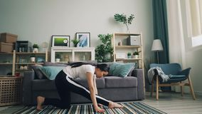 Flexibles asiatisches Mädchen tut, die Übungen zu Hause ausdehnend, welche die Yogahaltungen üben allein, die ihre Gesundheit und stock footage