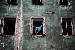 Flexibles Mädchen, das in einer Balletthaltung in den Ausstellfenstern auf der Fassade eines alten verlassenen Gebäudes steht Lizenzfreies Stockfoto