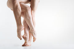 Flexile graceful dancers legs performing in the white colored room Royalty Free Stock Image