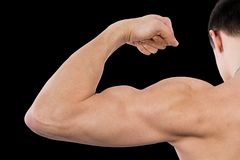 Flexing biceps isolated on black Royalty Free Stock Image
