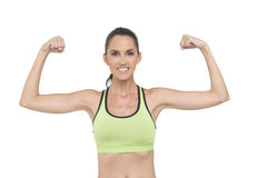 Flexing fit woman. An attractive, fit woman, wearing a sports bra flexes her muscles Stock Images
