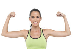 Flexing fitness woman. An attractive fit woman, flexes her muscles. Photogrpahed in studio Stock Photo