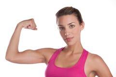 Flexing woman. A fit woman flexes her bicep Stock Photos