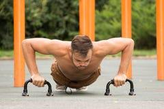 Flexiones de brazos del entrenamiento del modelo de la aptitud del hombre al aire libre Imagen de archivo