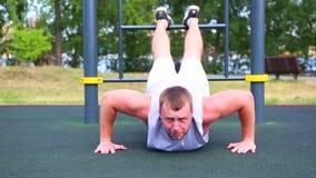Flexiones de brazos de la motivación del deporte del piso El atleta positivo joven hace pectorales en el punto del punto de la ca almacen de video