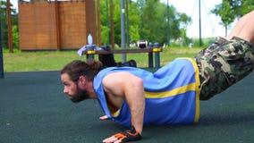 Flexiones de brazos de la motivación del deporte del piso El atleta positivo joven hace pectorales en el punto del punto de la ca almacen de metraje de vídeo