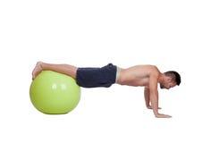 Flexiones de brazos practicantes del hombre fuerte con una bola grande Fotografía de archivo