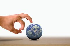 Flick it. A Male hand flicking the earth on a wooden surface Royalty Free Stock Images