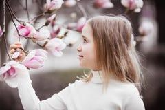 Flicka 8-9 år gammal stående Rymmer en filial av ett magnoliaträd Trädet blommar i stora rosa blommor fotografering för bildbyråer