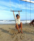 Flicka 11 år i hängmattan på stranden med havet i bakgrund Royaltyfri Bild
