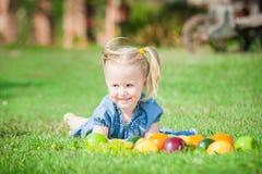 Flicka åt färgrika frukter på grönt gräs i räkning Royaltyfri Bild
