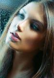 Flicka bak det våta exponeringsglaset Arkivfoto