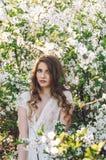Flicka bland körsbärsröda blomningar Arkivfoton