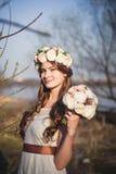 Flicka, blom- krans och vårskog Arkivbilder