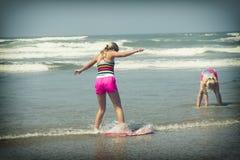 Flicka eller tonårigt lära för att rida en skimboard på den Oregon kusten Arkivfoto