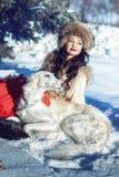 Flicka en pälsväst och en röd kjol som ligger med hunden i snön Royaltyfri Bild