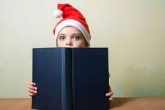 Flicka för Ð-¡ ute i den Santa Claus hatten med den stora blåa boken Ð-¡ hristmas Arkivfoto