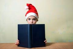 Flicka för Ð-¡ ute i den Santa Claus hatten med den stora blåa boken Ð-¡ hristmas Royaltyfri Bild