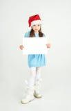 Flicka för Ð-¡ ute i den Santa Claus hatten med ett vitt ark för tomt papper Ð-¡, Royaltyfri Foto
