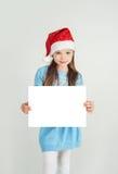 Flicka för Ð-¡ ute i den Santa Claus hatten med ett vitt ark för tomt papper Ð-¡, Arkivfoton