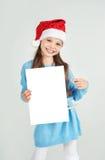 Flicka för Ð-¡ ute i den Santa Claus hatten med ett vitt ark för tomt papper Ð-¡, Royaltyfri Fotografi
