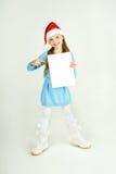 Flicka för Ð-¡ ute i den Santa Claus hatten med ett vitt ark för tomt papper Ð-¡, Arkivbild