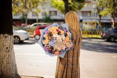 Flicka för bakre sikt som rymmer en härlig bukett av olika blommor arkivbild