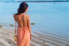 Flicka för baksiktsbrunett med långt hår i strandklänning och vide- påse på den långa remmen som poserar på stranden royaltyfri foto
