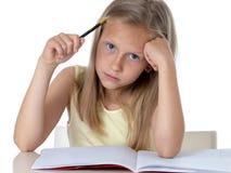 Flicka för barnskolastudent som ser olycklig och trött i utbildning royaltyfria bilder