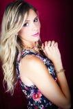 Flicka för blont hår för stående härlig med smink och röd bakgrund royaltyfri foto