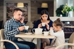 Flicka för Caucasian moder och för litet barn i restaurang medan deras talande mobiltelefon för upptagen fader Arkivfoto