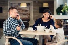 Flicka för Caucasian moder och för litet barn i restaurang medan deras talande mobiltelefon för upptagen fader Royaltyfri Foto