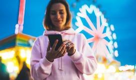 Flicka för främre sikt som pekar fingret på skärmsmartphonen på ljus för defocusbakgrundsbokeh i aftongatadragningen, använda för royaltyfri bild