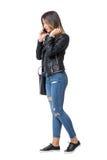 Flicka för gatastilmode som går, medan tala på telefonen och justera hår Arkivfoto
