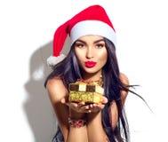 Flicka för julmodemodell som rymmer den guld- gåvaasken royaltyfri foto