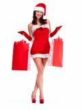 Flicka för jultomtenhjälpredajul med shoppingpåsar. Arkivbilder