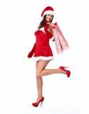 Flicka för jultomtenhjälpredajul med shoppingpåsar Arkivfoto