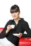 flicka för kaffekopp som har restsofaen Royaltyfri Foto