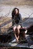 Flicka för krabbt hår för brunett i bergen, sitta som är sexigt på en massiv trätabell royaltyfria bilder