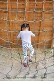 Flicka för liten unge för bakre sikt på lekplatsen som spelar på att klättra det netto repet arkivbild