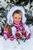 Flicka för liten unge i vintertumvanten under granträd royaltyfri foto