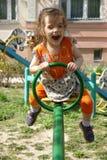Flicka för liten unge som har gyckel på lekplats på solig vårdag Fotografering för Bildbyråer