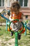 Flicka för liten unge som har gyckel på lekplats på solig vårdag Royaltyfri Fotografi