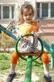 Flicka för liten unge som har gyckel på lekplats på solig vårdag Arkivbilder