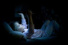 Flicka för litet barn som hemma använder minnestavlateknologi i säng vid natt Allvarlig eller toughtful ungedotter, i att hålla ö Arkivfoto