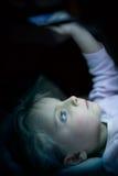 Flicka för litet barn som hemma använder minnestavlateknologi i säng vid natt Allvarlig eller toughtful ungedotter, i att hålla ö Royaltyfria Foton